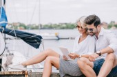 Fotografie smiling young couple in sunglasses sitting and using digital tablet near yacht