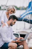 Fotografie side view of smiling girl looking at handsome man in sunglasses using laptop on yacht