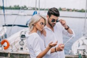 Fotografie beautiful stylish young couple in sunglasses using digital tablet on yacht
