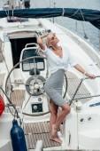 Fotografia bella donna bionda sorridente in occhiali da sole in posa vicino al volante su yacht