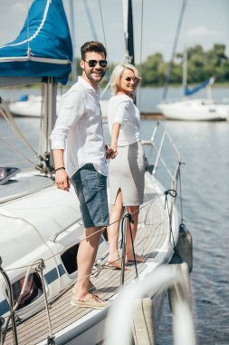 beautiful happy young couple in sunglasses holding hands and smiling at camera on yacht