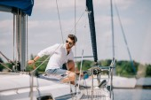 handsome young man in sunglasses looking away while sitting on yacht