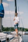 Fotografia vista integrale del giovane bello in occhiali da sole in piedi sullo yacht