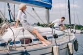 schöne junge Frau sitzt auf Yacht und Blick auf den Mann hinter