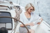 smiling blonde girl in sunglasses using digital tablet while sitting on yacht
