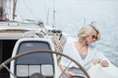 fiatal nő napszemüveg segítségével digitális tabletta és ellenőrzési karóra, ülve a yacht