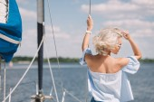 Fotografie rear view of beautiful young blonde woman in sunglasses looking away while standing on yacht