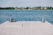 empty wooden pier and blue water at sunny day