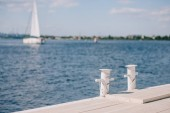 Fotografie prázdná dřevěná mola a yacht na pozadí v letním dni