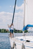 Fotografie beautiful young couple waving hands while standing together on yacht