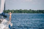 gyönyörű szőke nő a bikini állva yacht