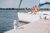 Fotografia fuoco selettivo del pilastro di legno e giovane coppia su yacht dietro
