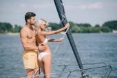 a gyönyörű fiatal pár fürdőruha átölelve, miközben állt össze a jacht oldalnézete