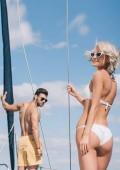 šťastný mladý pár v plavky a sluneční brýle, tráví čas spolu na jachtě