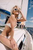 Fotografie selective focus of smiling woman in bikini and her boyfriend behind on yacht