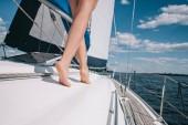 levágott kép lábak fiatal nő séta a yacht