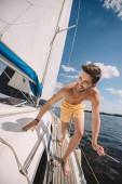 usmívající se muž košili v plavky běžící na jachtě