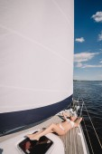 Fotografie attractive young woman in swimwear relaxing and having sunbath on yacht