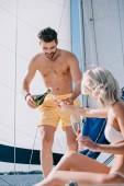 uomo senza camicia bello in calzoncini da bagno versando champagne nel bicchiere della ragazza su yacht