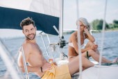 smiling couple in swimwear relaxing with champagne glasses on yacht