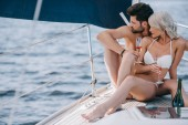 young couple in swimwear sitting with champagne glasses on yacht