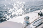 selective focus of yacht and sun glares on water surface
