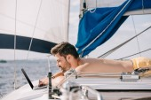 side view of smiling shirtless man using laptop on yacht
