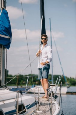 full length view of handsome young man in sunglasses standing on yacht