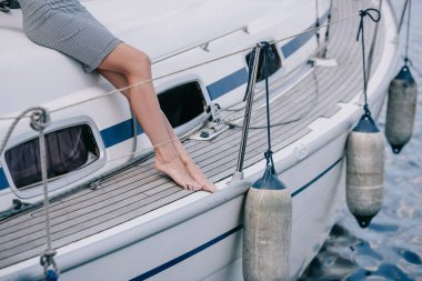 cropped shot of young barefoot woman sitting on yacht