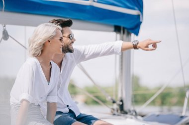 happy young couple in sunglasses looking away while sitting together on yacht