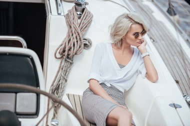 High angle view of pensive blonde girl in sunglasses sitting on yacht and looking away stock vector