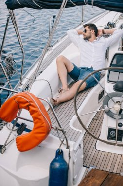 high angle view of handsome young man in sunglasses looking away while resting on yacht