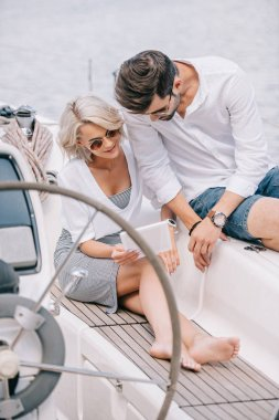 stylish young couple in sunglasses using digital tablet on yacht