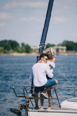 beautiful happy young couple in sunglasses sitting and hugging on yacht