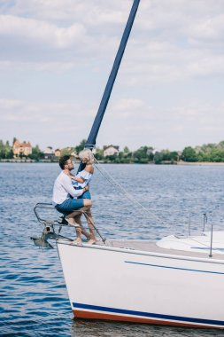 side view of beautiful happy young couple sitting and hugging on yacht