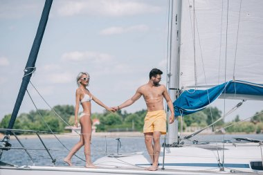 beautiful young couple in swimwear and sunglasses holding hands while spending time together on yacht