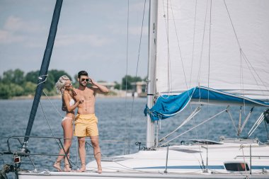 beautiful young couple in swimwear and sunglasses standing together on yacht