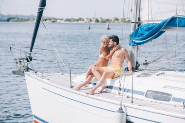 happy young couple in swimwear and sunglasses hugging while sitting together on yacht