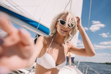 selective focus of beautiful girl in swimwear and sunglasses smiling at camera on yacht