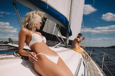 selective focus of attractive woman in bikini having sunbath and her boyfriend behind on yacht