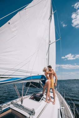 smiling young couple in swimwear embracing on yacht