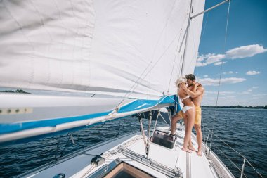 distant view of young couple in swimwear embracing on yacht