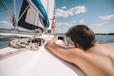 Selective focus of man taking picture of girlfriend on smartphone on yacht stock vector