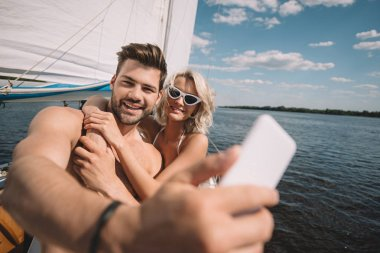 smiling young couple taking selfie on smartphone on yacht
