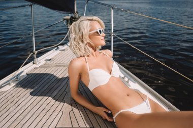 attractive young woman in sunglasses and swimwear relaxing and having sunbath on yacht