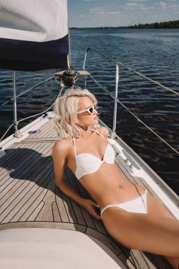 beautiful young woman in swimwear and sunglasses relaxing and having sunbath on yacht