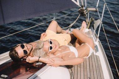 smiling couple in sunglasses and swimwear having sunbath on yacht