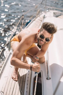 smiling shirtless man in sunglasses pulling rope on yacht