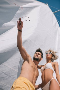 low angle view of shirtless man in swimwear pointing by hand to girlfriend on yacht