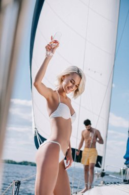 smiling woman in bikini holding champagne glass and her boyfriend walking behind on yacht